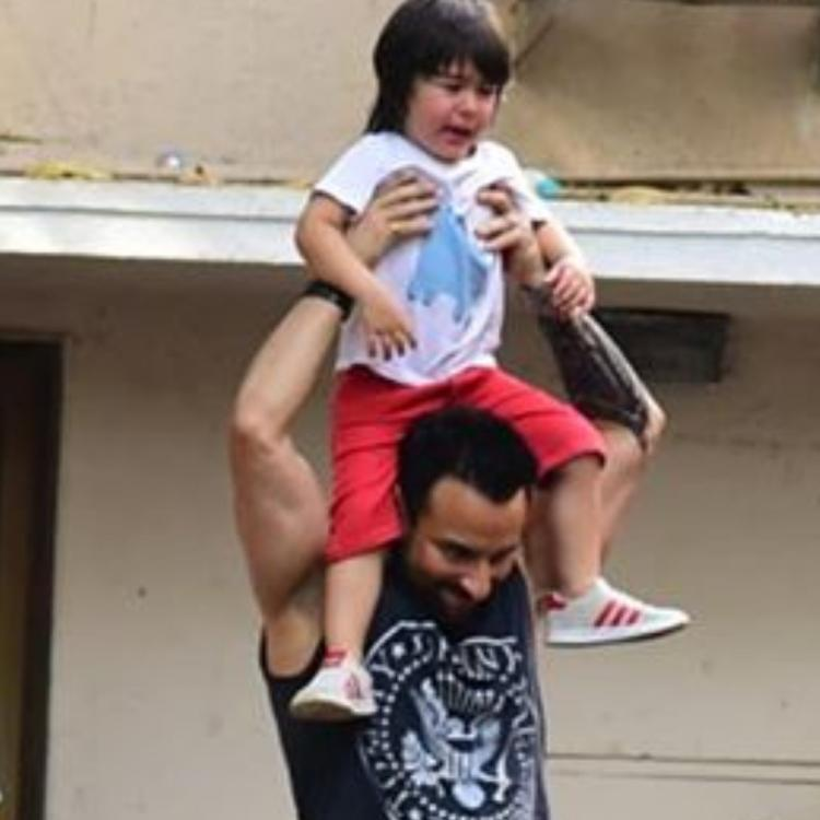 Saif Ali Khan tries to cheer up a crying Taimur Ali Khan by taking him for a ride on his shoulders; See Pic
