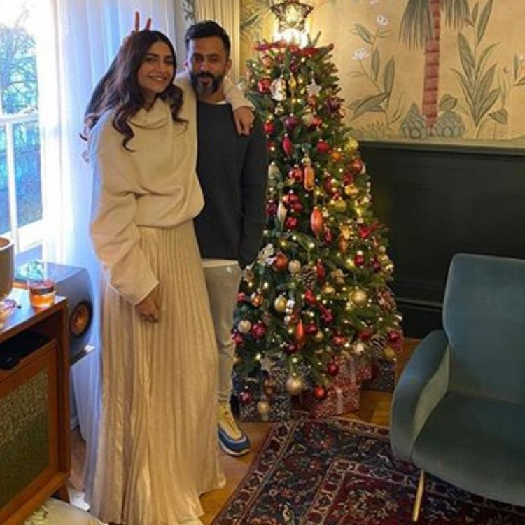 Sonam Kapoor & Anand Ahuja make for an adorable duo as they pose next to a Christmas tree and wish their fans
