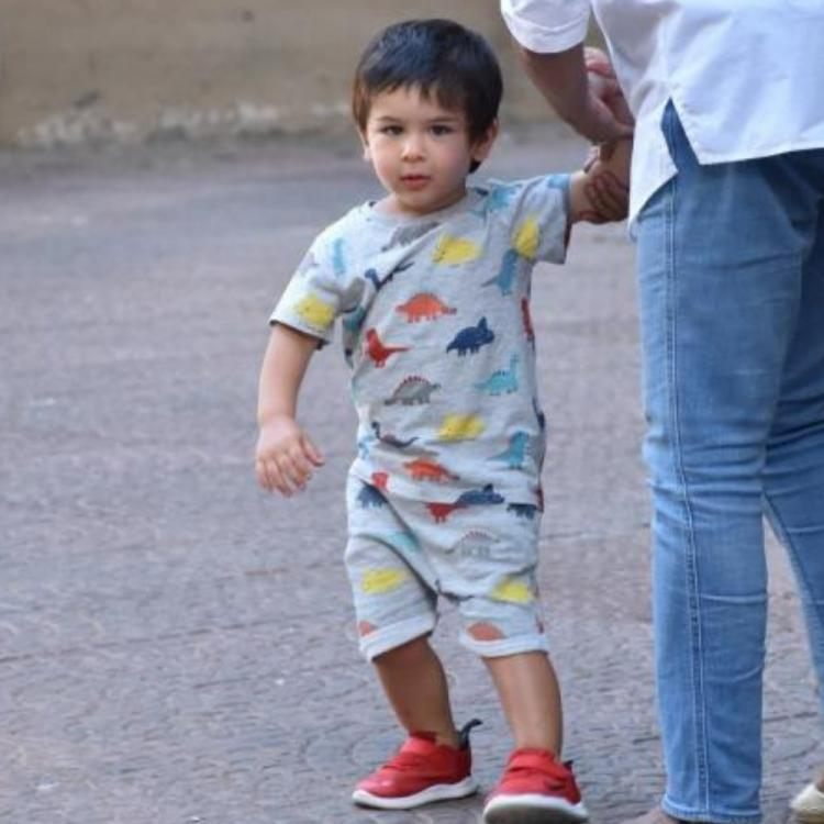 Taimur Ali Khan flashes his smile as he poses for a PHOTO with his puppy and our hearts our melting