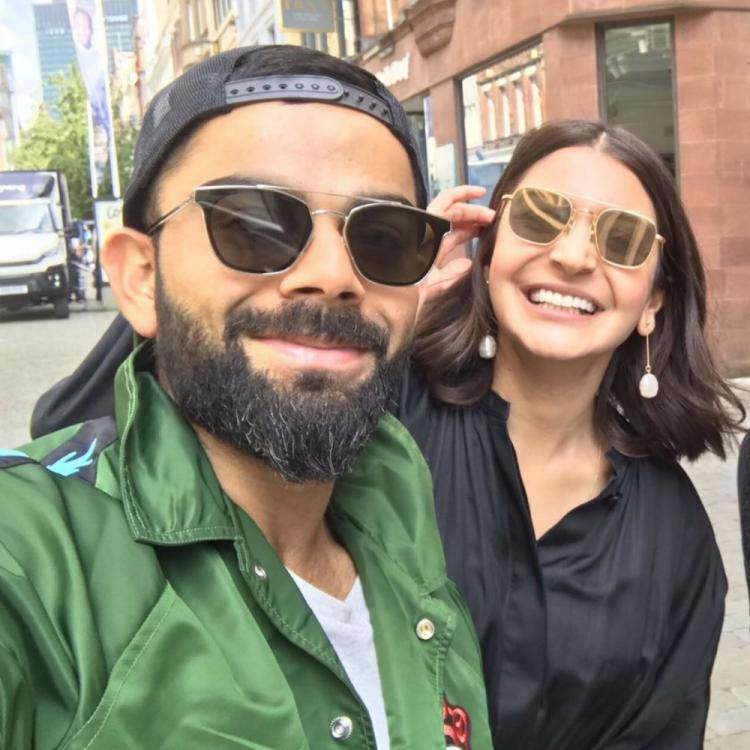 Anushka Sharma and Virat Kohli look happy and content as they pose with a fan; View PIC